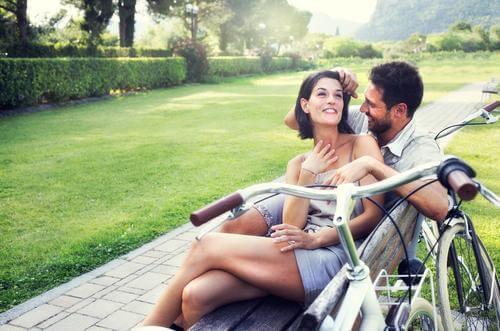 happy couple cuddling on park bench