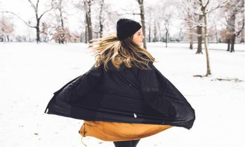 Woman twirling in snow