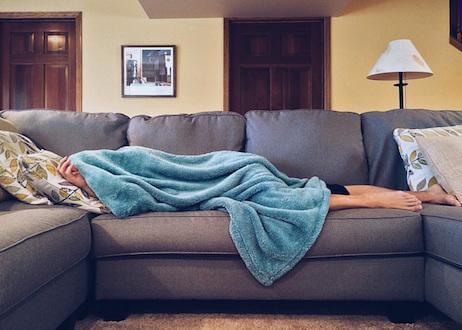 Person sleeping underneath blanket