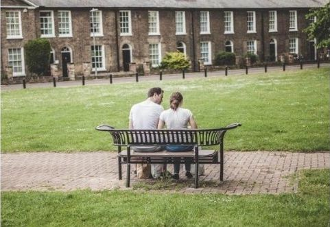 Father sitting with his daughter talking on a park bench.