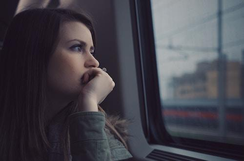Woman looking out a train window contemplatively