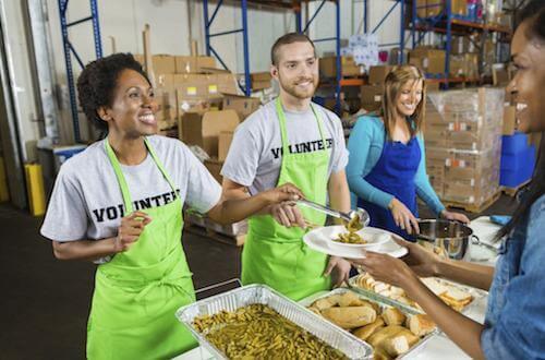 a group of people volunteering serving food