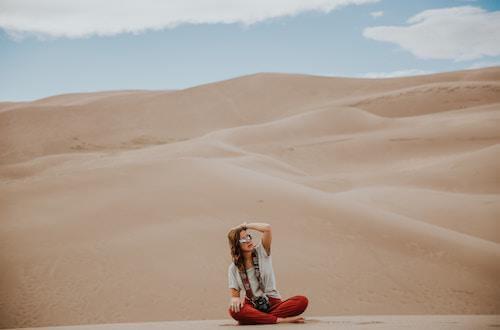 Woman sitting on sand dunes