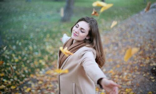 Woman swirling in autumn leaves