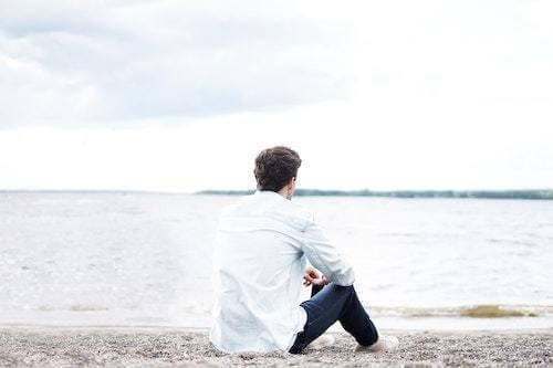 man sitting alone on a beach